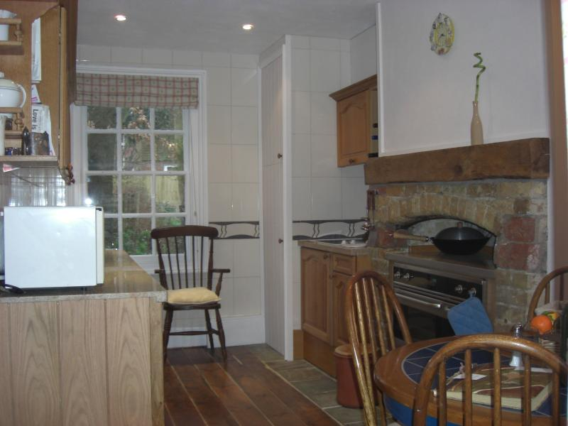 fully equipped open plan kitchen with granite worktops, fireplace incorporating a range oven, table