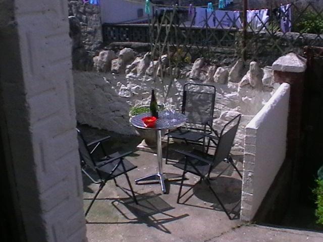 Dehors il est un petit jardin avec table et chaises.  Le jardin est un piège de vrai soleil.