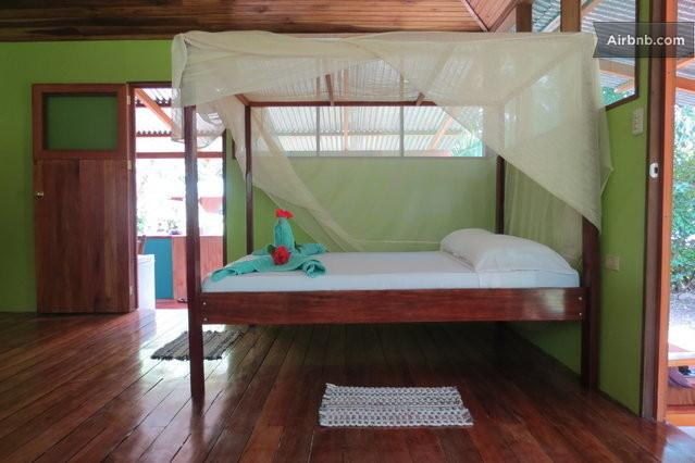 Inside Casa Lapa, view of one of the three beds available, peeking out to the veranda kitchen