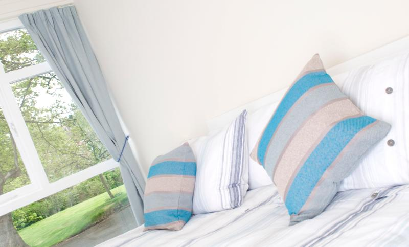 Spacious king bedroom with full length window and Berwick Law views