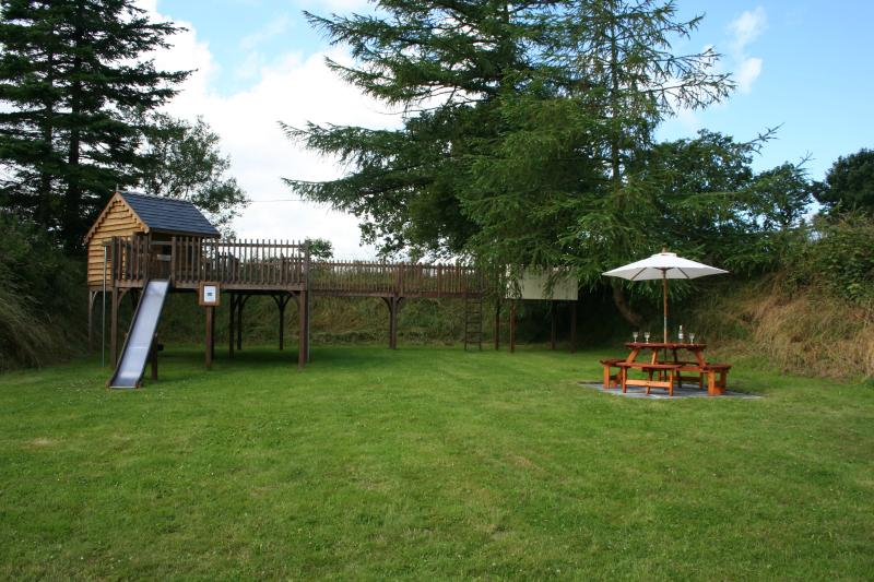 Play area with climbing wall, swings, slides, castle and Children's Cottage
