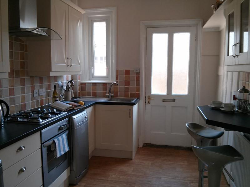 Fully fitted kitchen with breakfast bar and door onto private courtyard