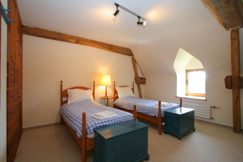 One of the two twin bedrooms which share the family bathroom where there is a shower over bath.