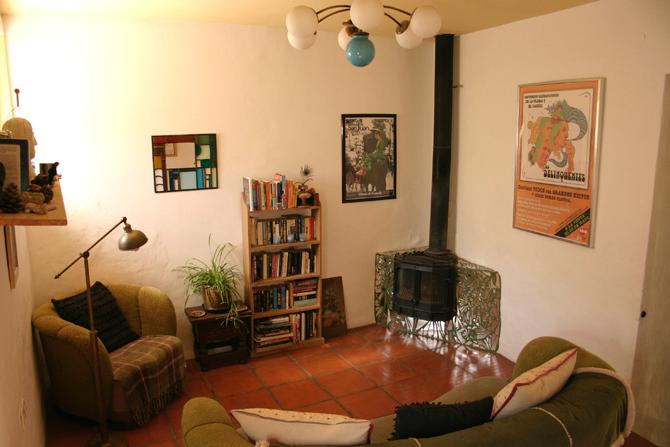 Cosy downstairs sitting room with lots of books and woodburner