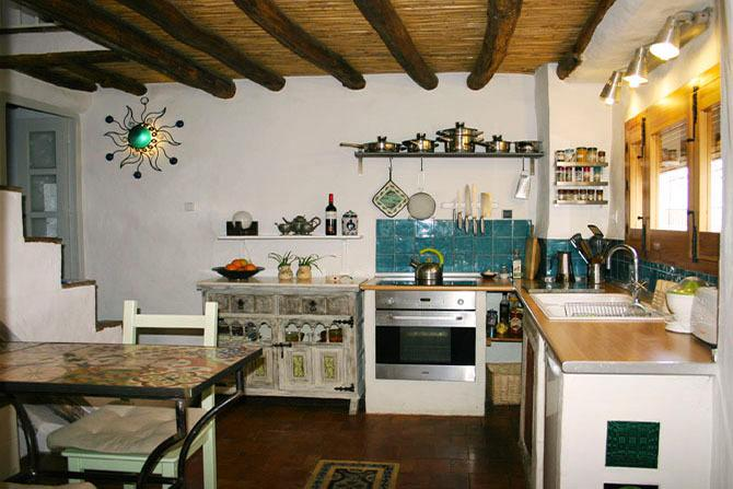 Handbuilt well-stocked kitchen with window looking onto pretty Andalucian street