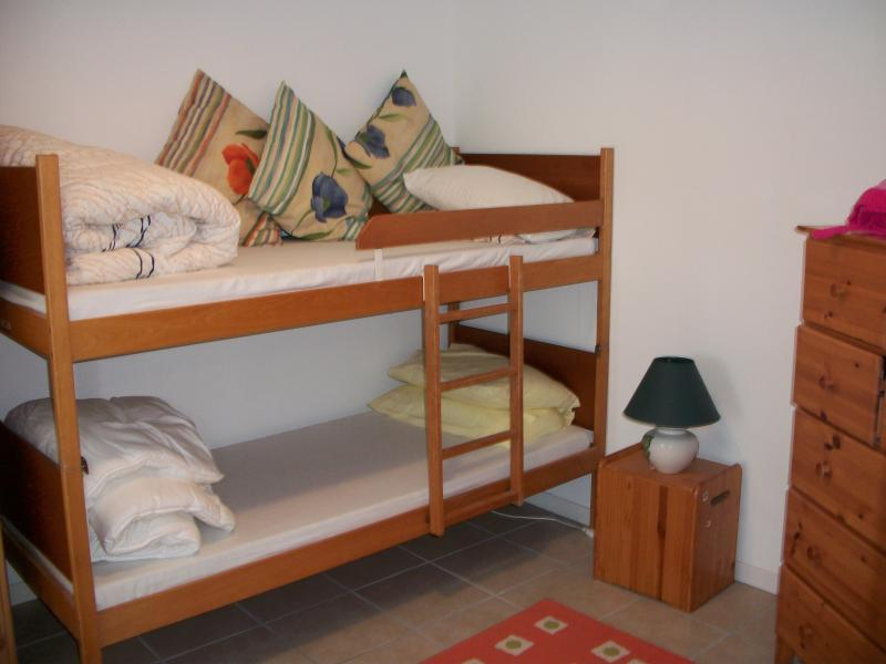 Bedroom with either bunk beds or adult sized single bed. Wardrobe and chest of drawers.