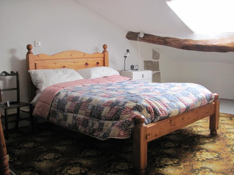 Chambre à coucher principale. VELUX de type fenêtre et côté mur. Petite armoire, chevet tiroirs.