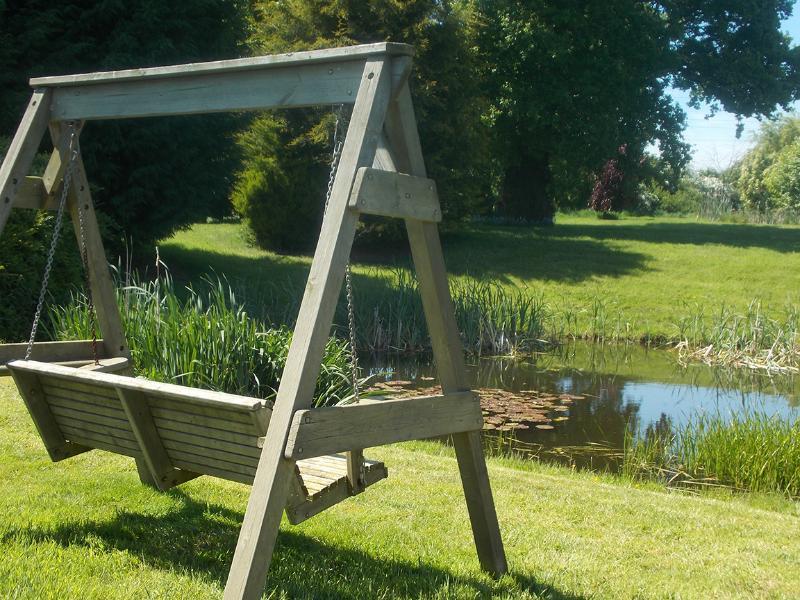 Silla del oscilación con vistas al estanque de los patos