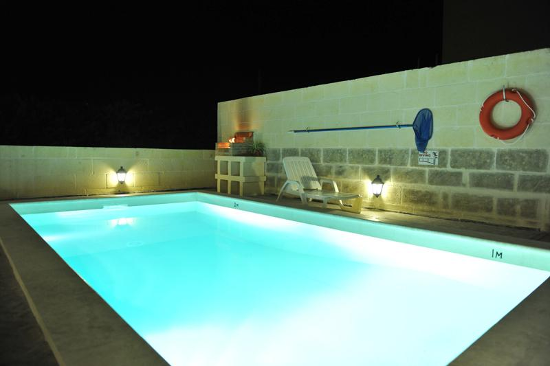 Pool and BBQ area at night