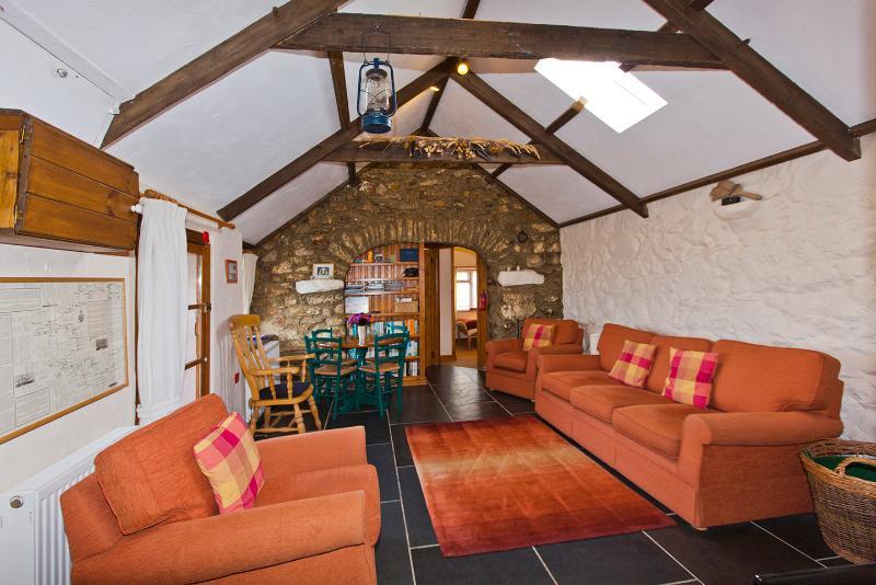 Le spacieux salon salle à manger. Un plafond voûté, dalles ardoises naturelles et un poêle à bois