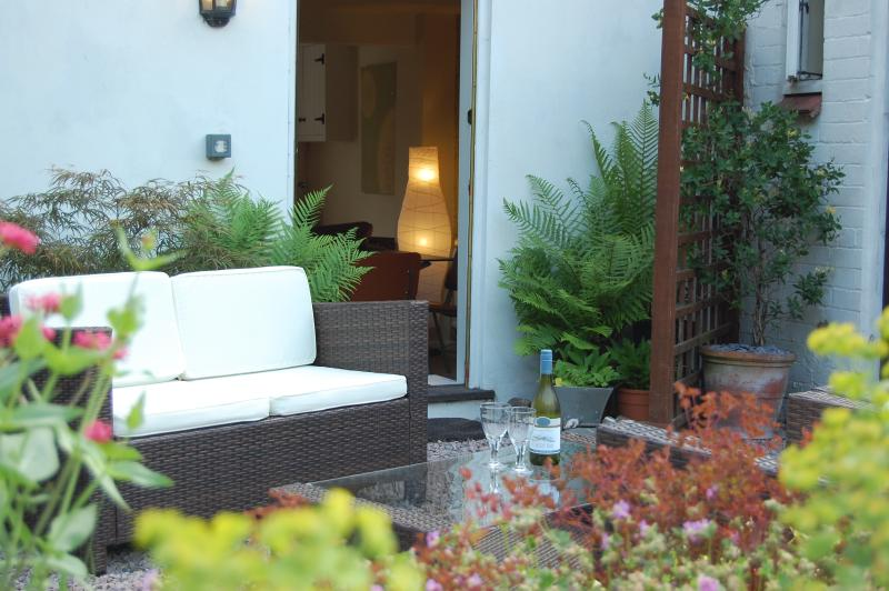 Relax and enjoy a glass of wine on a comfy sofa, in the private rear courtyard