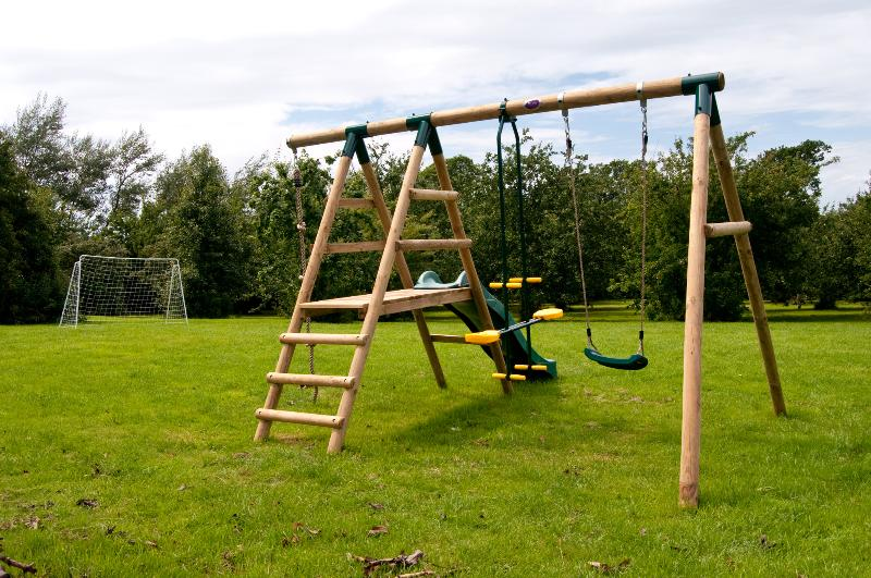 kids play area with swings and slide, bats and balls available on request