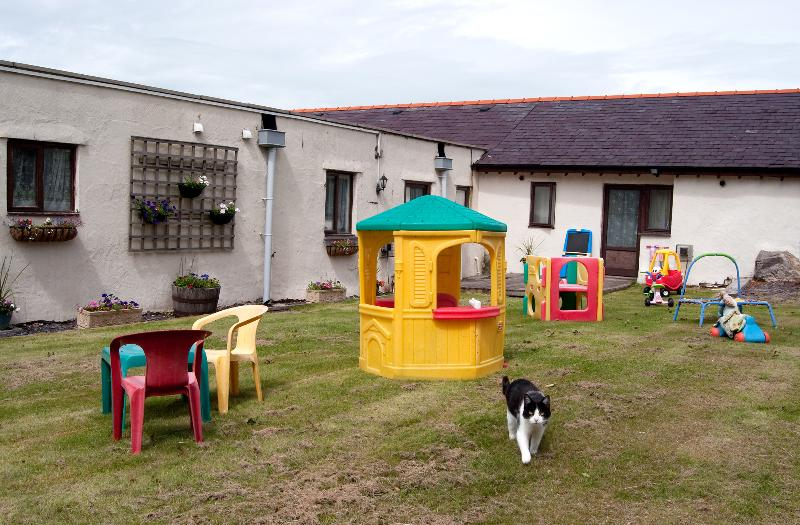 Rear of cottagers with secure gates and toys for the younger child and Tinker the cat]