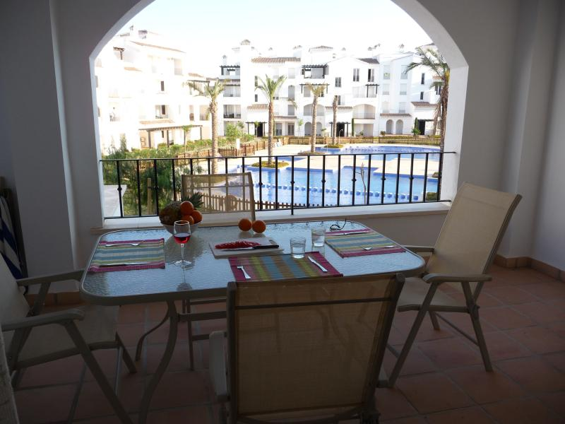 Spacious covered balcony with seating for six - pools and gardens  downstairs. Winter sun all day!