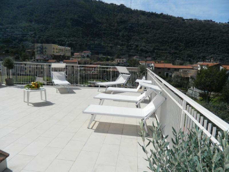 Exklusiv solterrass utrustad med solstolar, solstolar, dusch, bord, stolar och grill