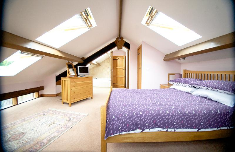 Light sunny upstairs bedroom with luxurious corner bath - cloakroom with toilet & basin screened