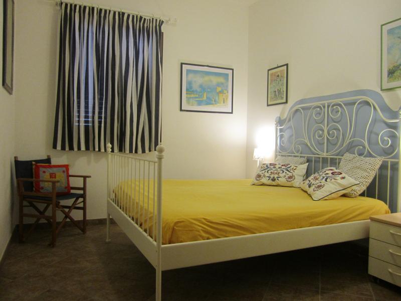 Camera matrimoniale con comodini, armadio a 3 ante, specchio, sedia in legno e aria condizionata