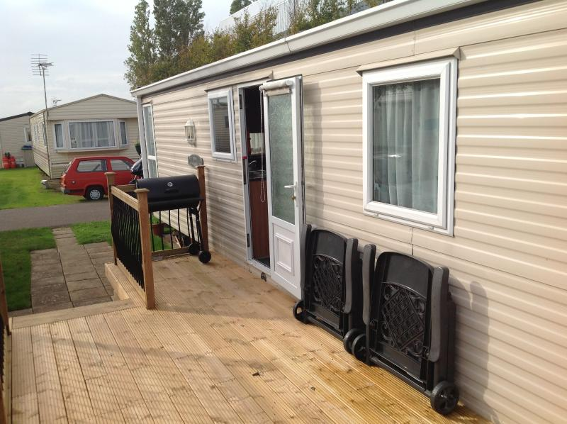 Ample decking with BBQ, sun loungers and table and chairs.