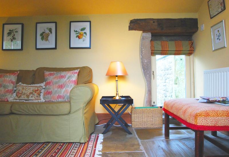 Soggiorno con tappeti e pavimento lastricato.