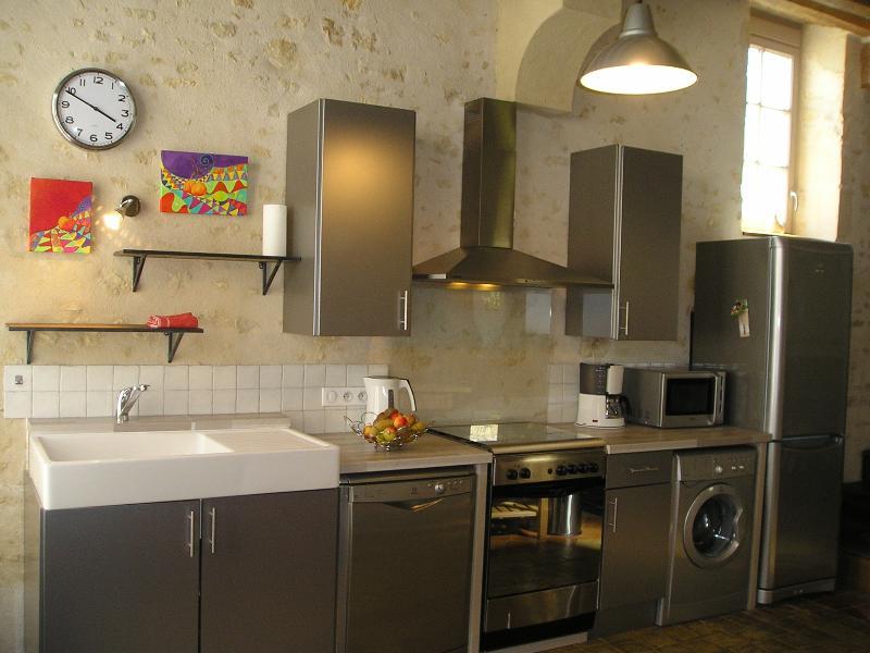 Espace cuisine : inox contemporain sur fond  de murs en pierres
