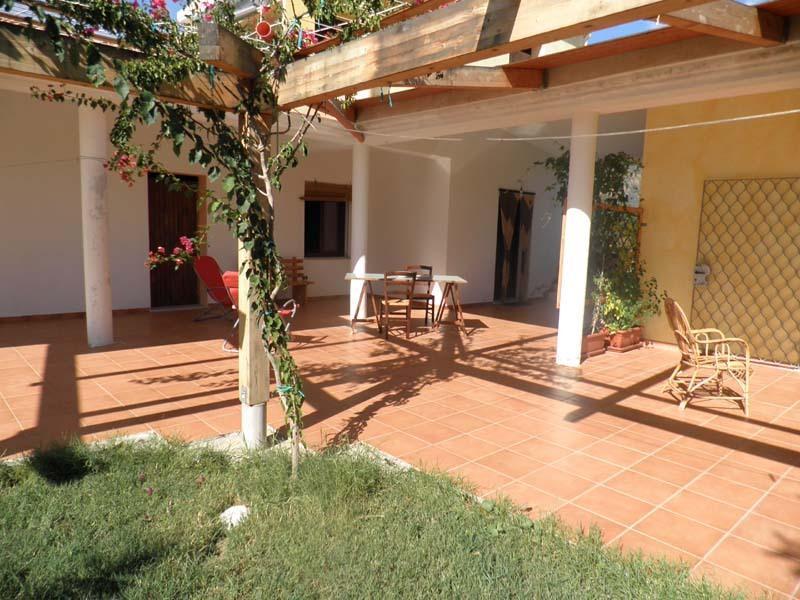Patio esterno con giardino e tavoli esterni
