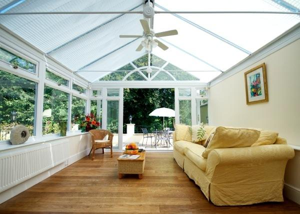 Conservatory with ceiling fan, full blinds, leads to large patio with garden furniture