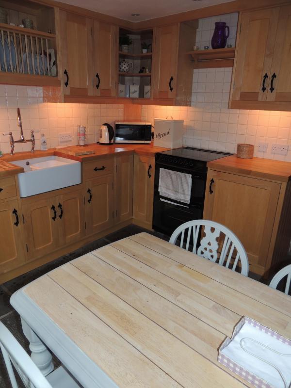 Cocina de madera maple, piso de losa y belfast fregadero con comodidades - lavadora/secadora y nevera ocultada