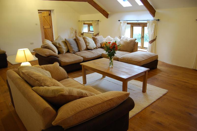 Another view of the huge lounge area which features oak flooring and lovely soft sofas.