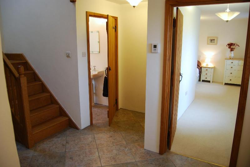 The spacious downstairs hallway leads to the kitchen/dining, cloakroom, utillity + bedroom 2.