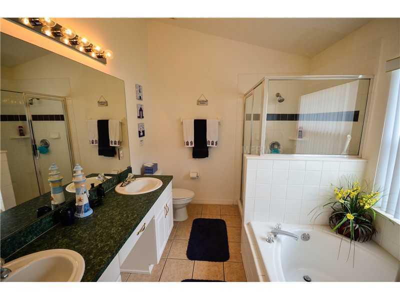 Salle de bain de la chambre principale avec ses lavabos, baignoire ovale et cabine de douche séparée.