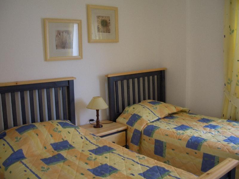 Spacious second bedroom. Twin beds, 6 drawer dresser, side table, built-ins  and air conditioned.