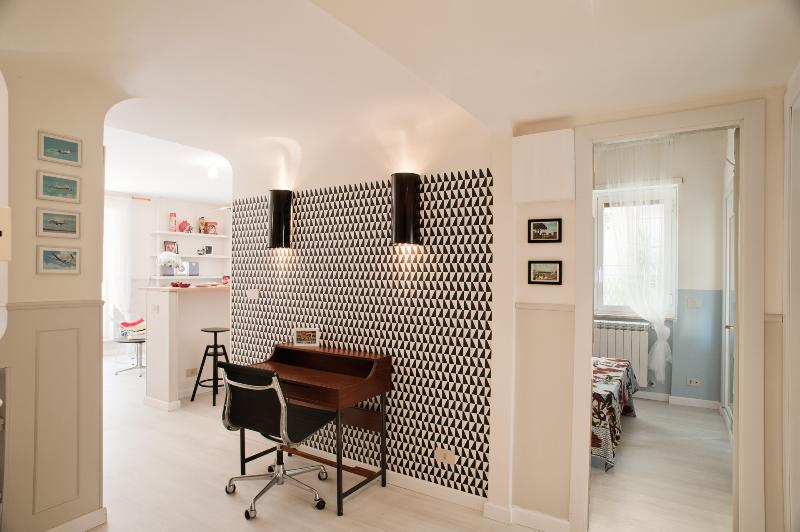 Studio area - swedish wallpaper, vintage desk and postcards, Eames aluminium chair, custom lights
