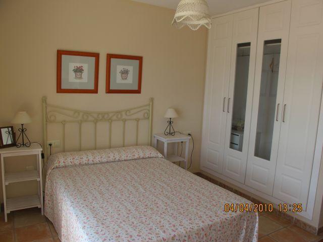 Dormitorio principal con armario empotrado, aire acondicionado, ventana y balcón