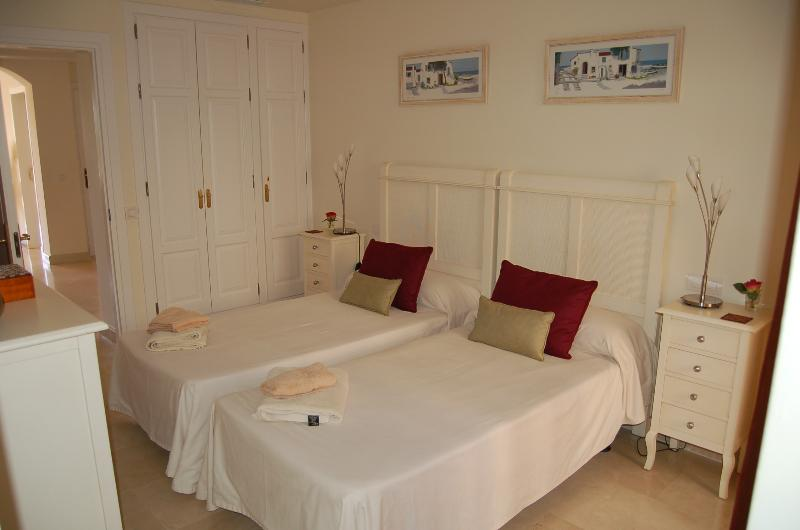 Bedroom 2 with twin beds, wardrobes, terrace and full en-suite bathroom
