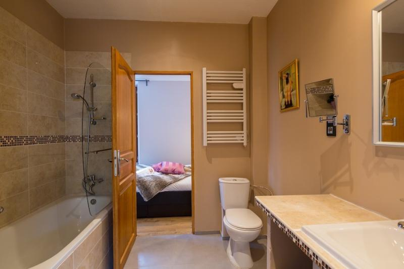 Comfy bathroom with bath, underfloor heating, towel heaters.