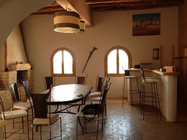 Une salle à manger avec cheminée et bar, donnant sur une terrasse.