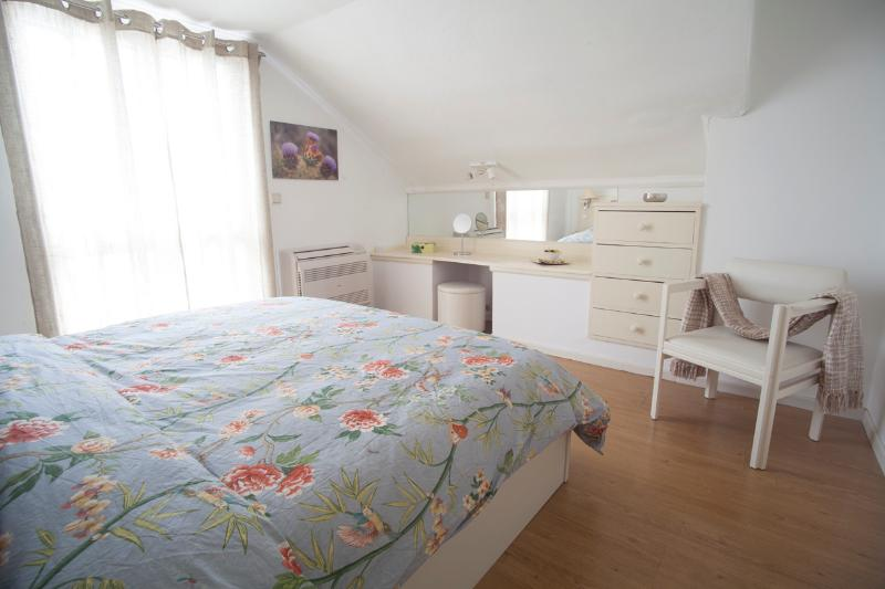 The bedroom is spacious, has air-conditioning and a balcony with castle and mountain views.