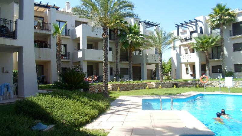 View of the apartment, pool area, and landscaped gardens