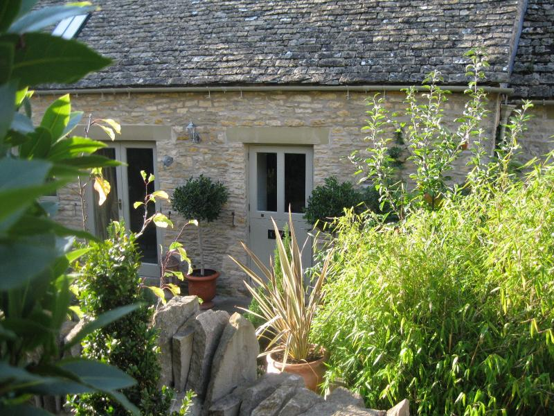 Quaint cottage garden with outdoor seating for two.