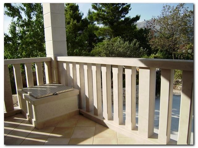 Balcony with a traditional stone balustrade & and a view of green area