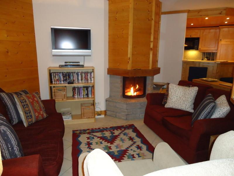 Open-plan sitting/dining/kitchen with underfloor heating and log-burning fireplace, balcony.
