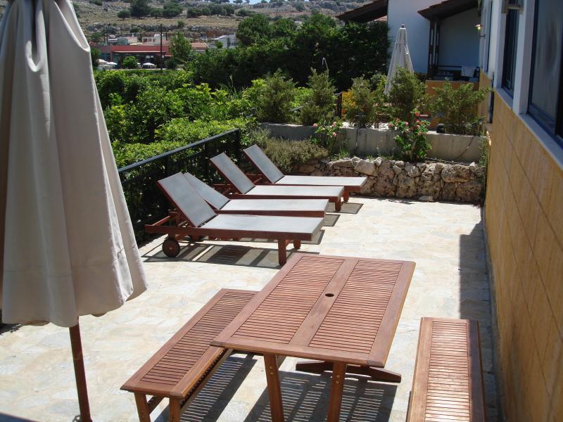 Driftwood patio with loungers, picnic table and parasol