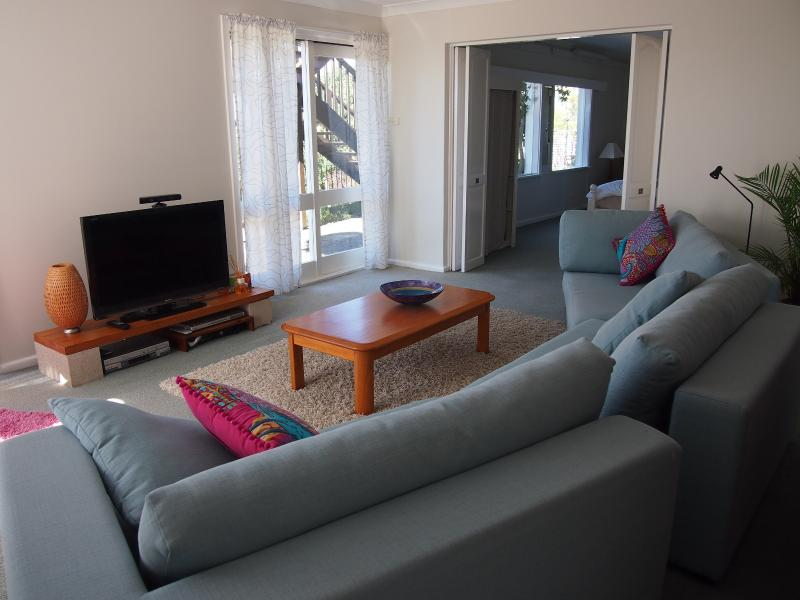 Lounge room with TV/DVD/video/x-box and sliding doors to garden