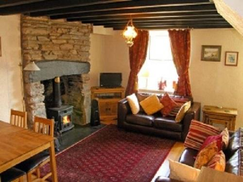 Warm and welcoming lounge with impressive inglenook fireplace and multi fuel wood burning stove