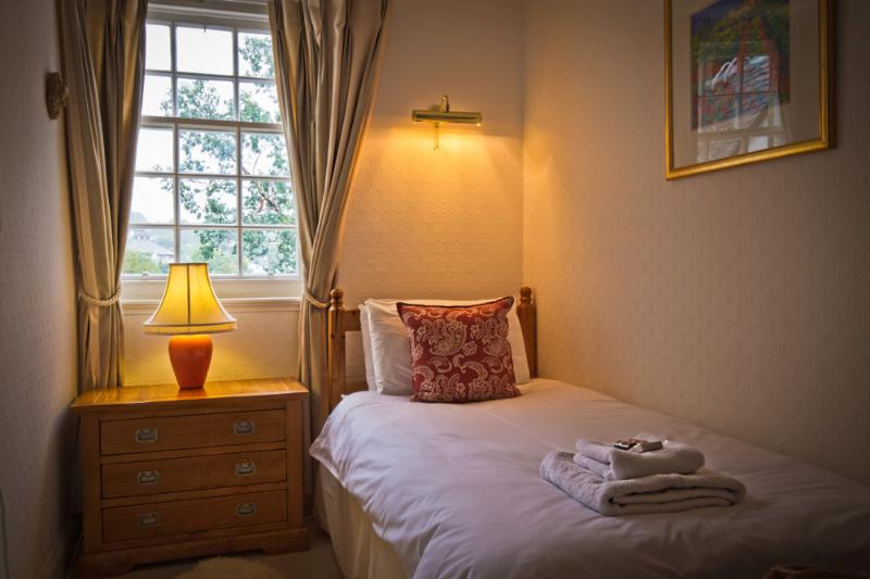 A peaceful single room overlooking the garden with a shower room opposite