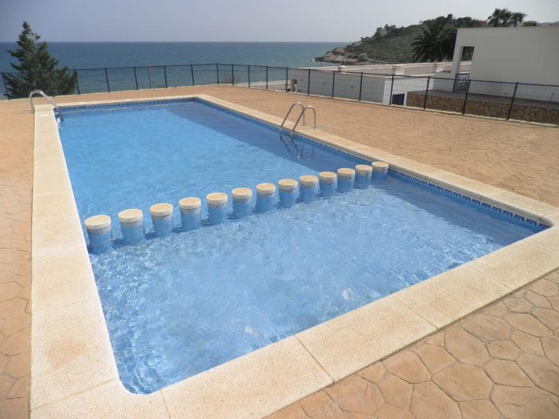 Great shared pool with sea view, sunbathing space, and childrens section.