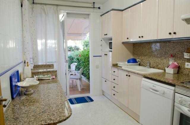 Cocina con electrodomésticos con la salida al jardín de alante
