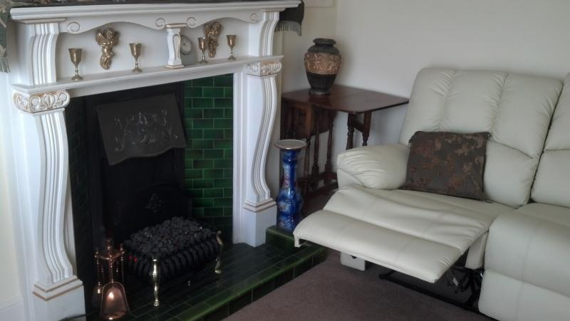 Main sitting room with leather sofas and leg rests and electric fire