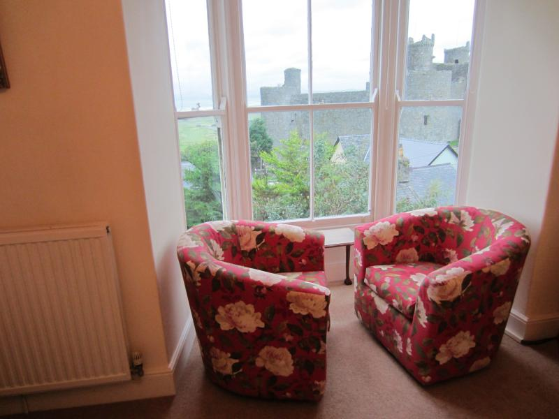 Swivel Chairs in bay window offering views of Harlech Castle, Cardigan Bay, Snowden
