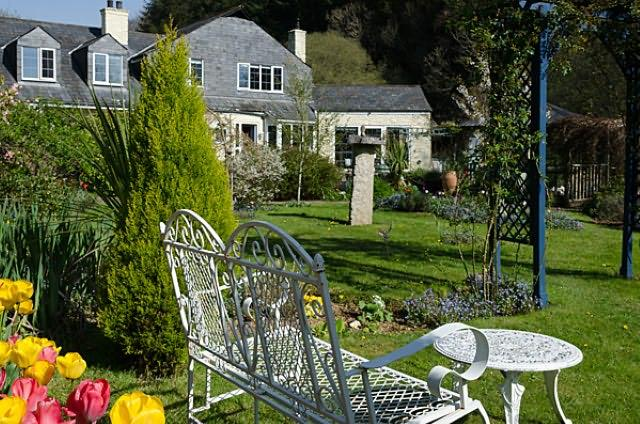 There is a patio area by the pond with garden furniture, ample private parking